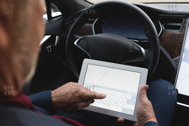 Mid section of businessman using digital tablet in a car