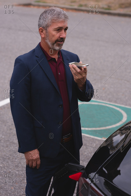 Mature businessman talking on mobile phone while charging electric car
