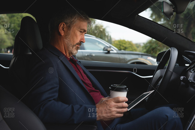 Side view of businessman using digital tablet in a car