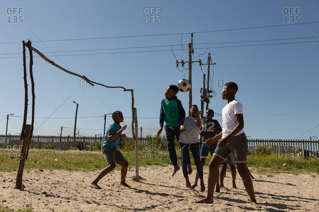 Kids playing football in the ground on a sunny day