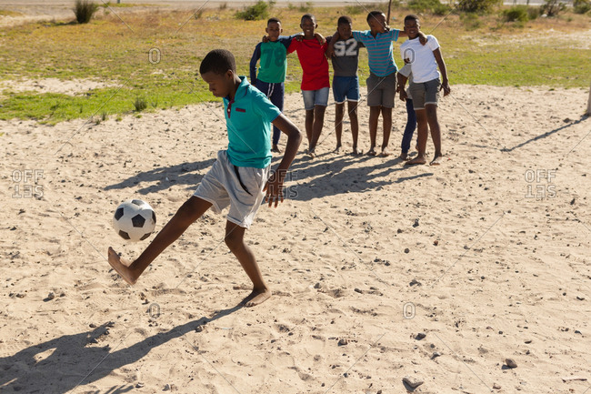 Boy playing football in the ground on a sunny day
