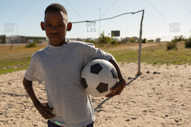 Boy holding football in the ground on a sunny day