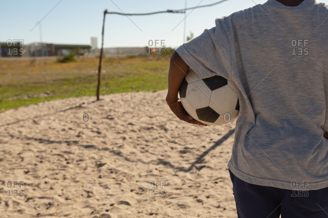 Rear view of boy holding football in the ground