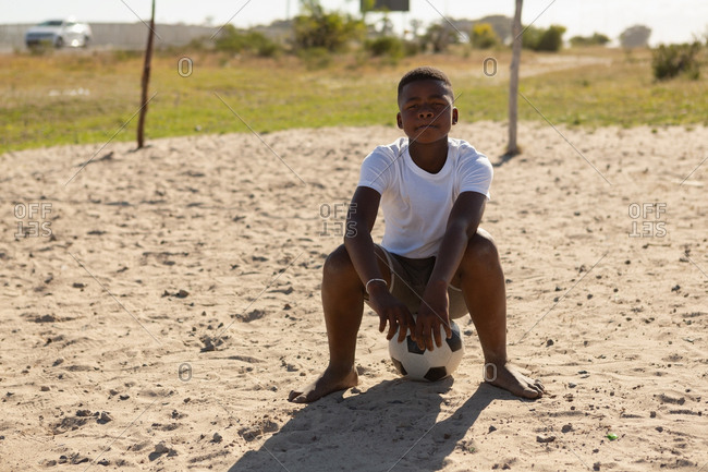 Portrait of boy sitting on football in the ground