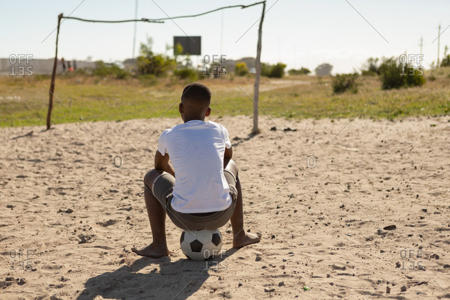 Rear view of boy sitting on football in the ground