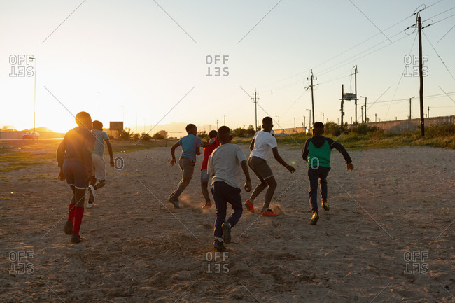 Kids playing football in the ground at dusk
