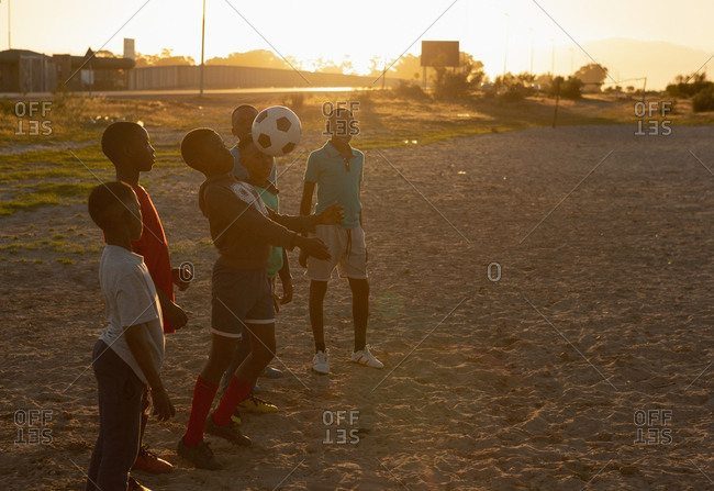 Kids playing with football in the ground at dusk