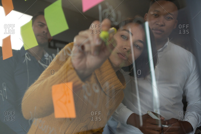 Female executive writing on glass wall in office