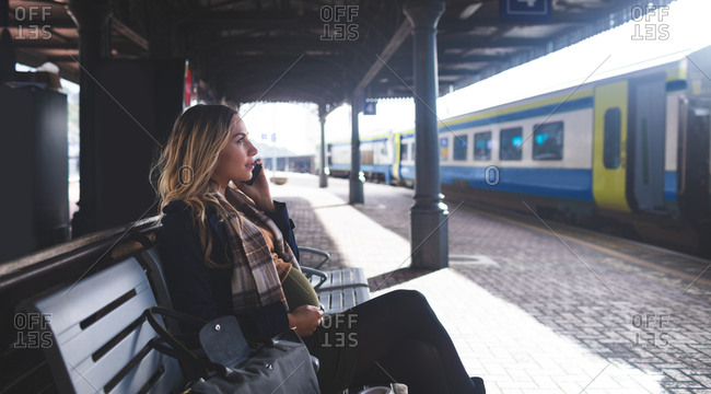 Side view of pregnant woman talking on mobile phone at railway station