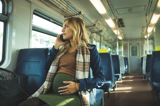 Beautiful pregnant woman talking on mobile phone while travelling in train