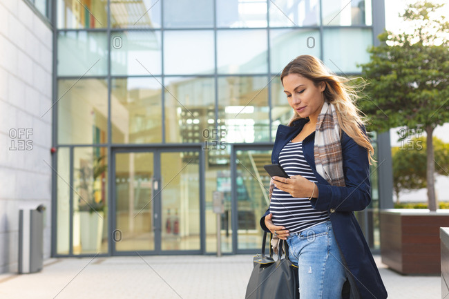 Pregnant woman using mobile phone in the city on a sunny day