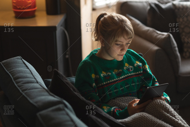 Woman using digital tablet on sofa in living room at home