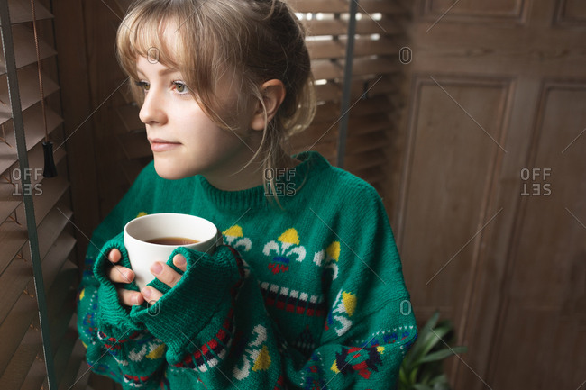 Woman looking through window while having coffee at home