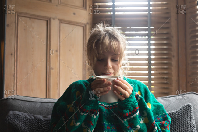 Woman having coffee while sitting on sofa at home