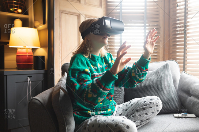 Woman using virtual reality headset on sofa in living room at home