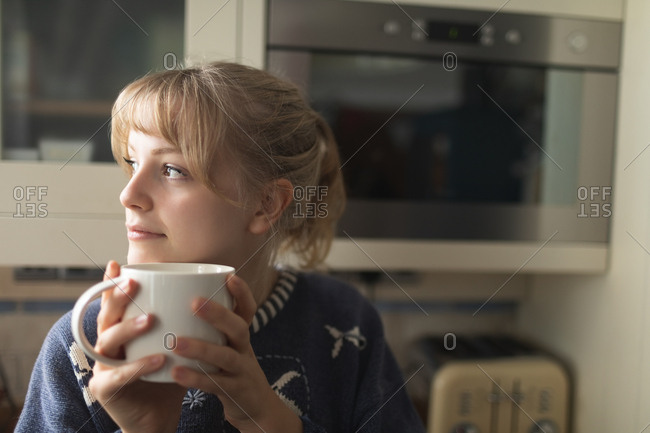 Beautiful woman having coffee in kitchen at home