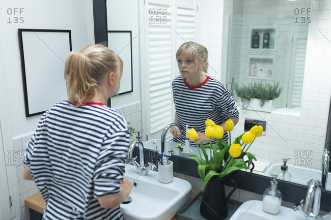 Beautiful woman looking in mirror at bathroom