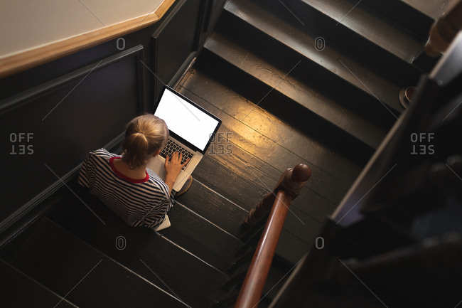 Overhead of woman using laptop on stairs at home