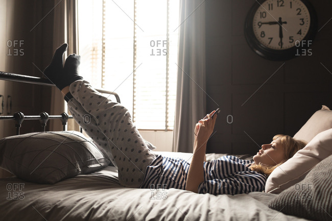 Side view of woman using mobile phone on bed in bedroom