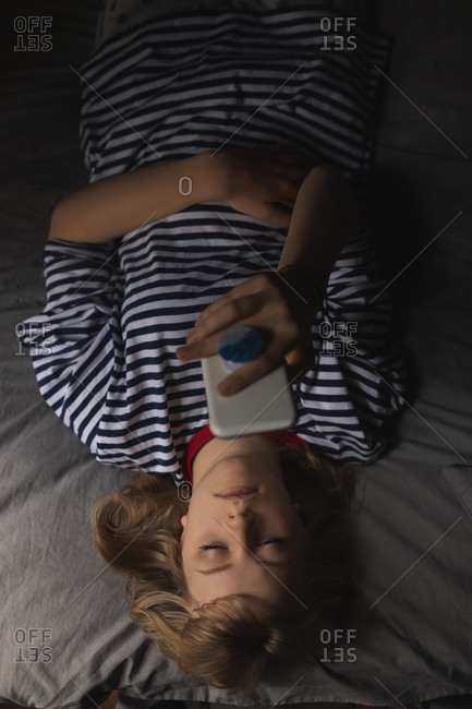 Woman using mobile phone on bed in bedroom at home
