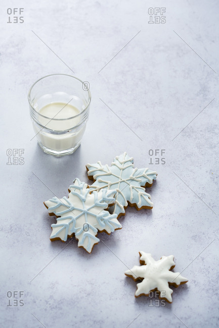 Three snowflake cookies with a glass of milk
