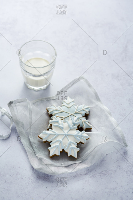 Two snowflake christmas cookies with milk