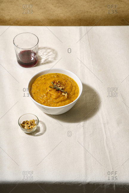 Pumpkin soup with a glass of wine on a table covered with linen tablecloth