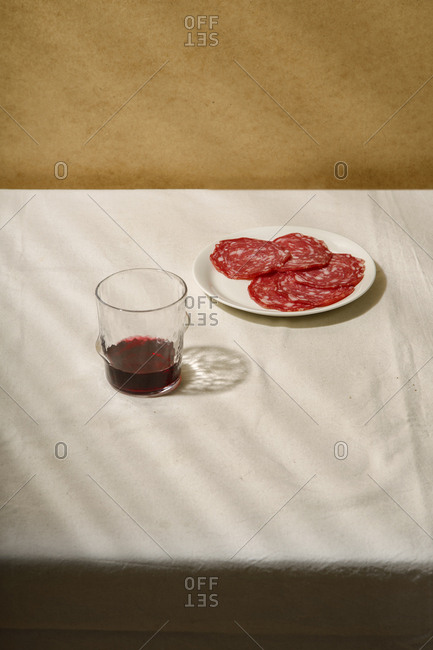 Minimalistic composition with salami slices on a white plate and a glass of wine