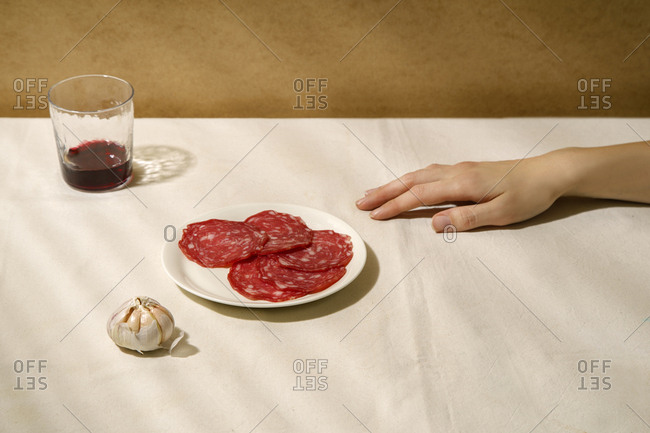Minimalistic composition with salami slices on a white plate, garlic, a glass of wine and female hand
