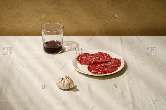 Minimalistic composition with salami slices on a white plate, garlic and a glass of wine