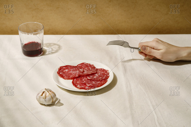 Minimalistic composition with salami slices on a white plate, garlic, a glass of wine and female hand holding fork