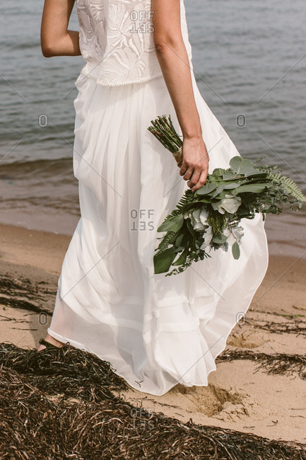 Bride walking along the beach with her bouquet