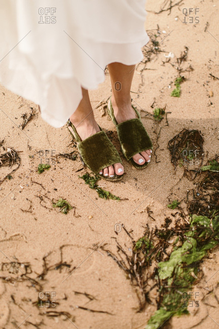 Woman standing close to seaweed on the beach