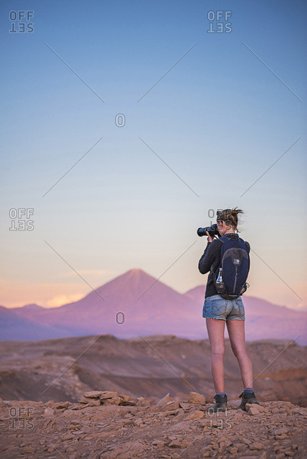 December 7, 2014: Chile, Antofagasta, San Pedro de Atacama, Atacama Desert, Person taking a photo at sunset of Licancabur Volcano, Atacama Desert