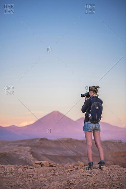 December 7, 2014: Chile, Antofagasta, San Pedro de Atacama, Atacama Desert, Person taking a photo at sunset of Licancabur Volcano, Atacama Desert