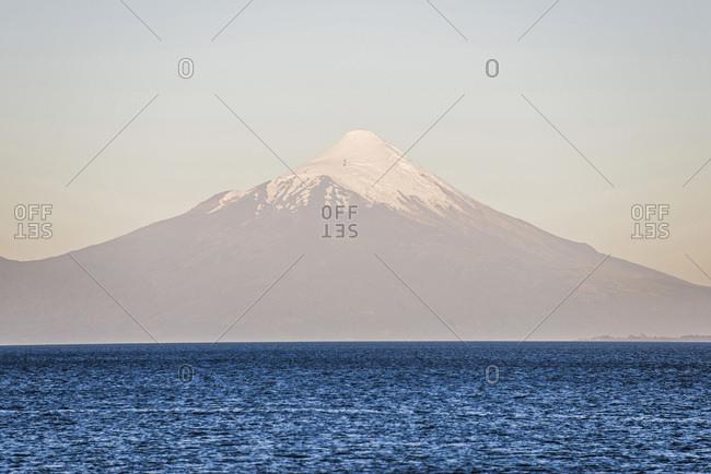 Chile, Los Lagos, Osorno Volcano at sunset, seen over Llanquihue Lake from Puerto Varas