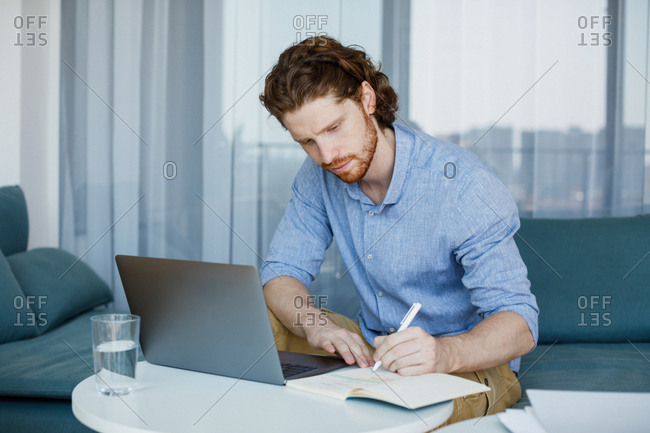 Serious Caucasian ginger businessman writing at his notebook.