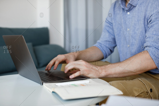 Hands of unrecognizable businessman typing on his laptop.