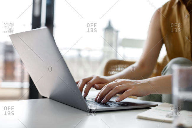 Hands of unrecognizable businesswoman typing on her laptop.