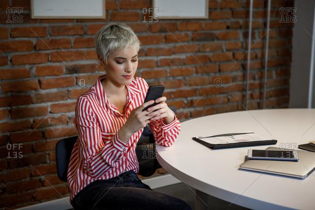 Beautiful stylish  Caucasian businesswoman using her smart phone at work.