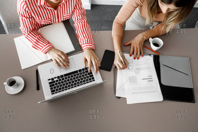 Two unrecognizable businesswomen working together using laptop.