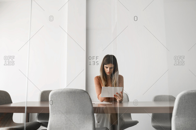 Pretty businesswoman sitting at meeting room and working on her tablet.