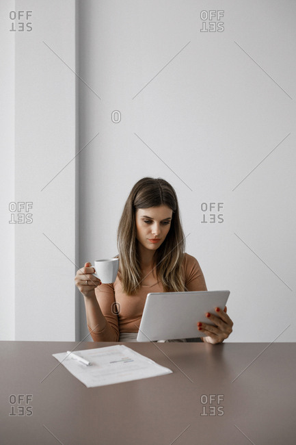 Beautiful Caucasian businesswoman reading on tablet an drinking coffee.