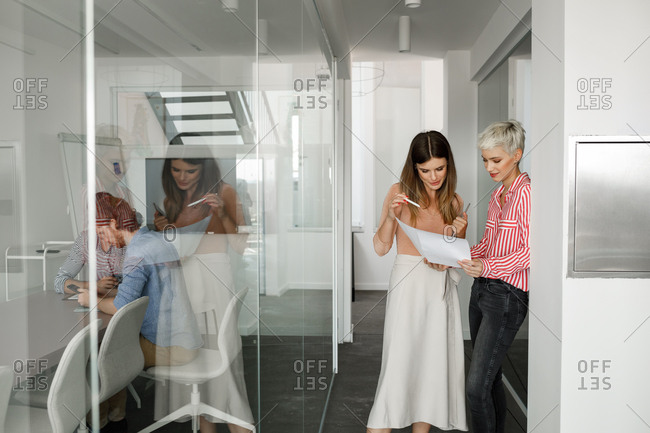 Two beautiful businesswomen standing on hallway and looking at paper document.