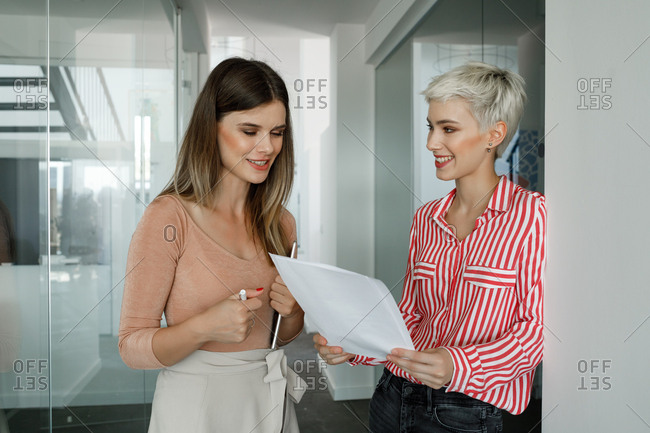 Two beautiful businesswomen standing on hallway and chatting.