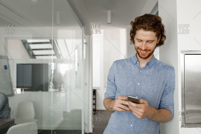Businessman standing on hallway and typing on his smart phone.