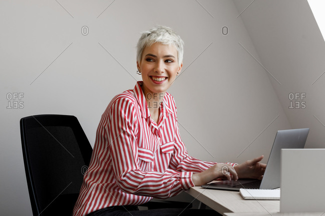 Portrait of beautiful smiling short-haired platinum blonde businesswoman.