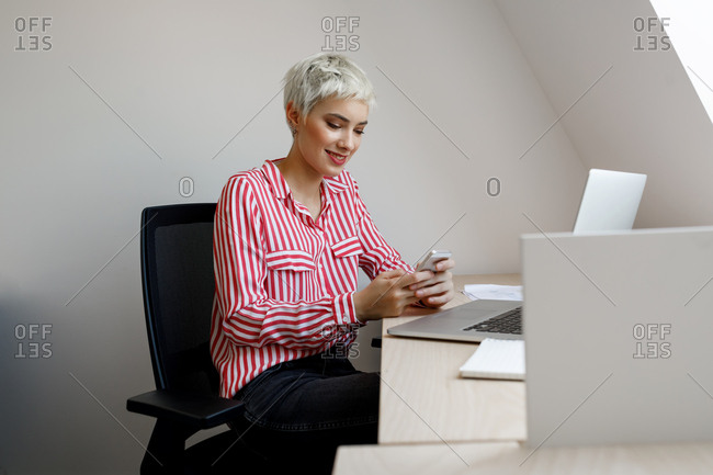 Beautiful young short-haired businesswoman sitting at her office and typing on her cell phone.