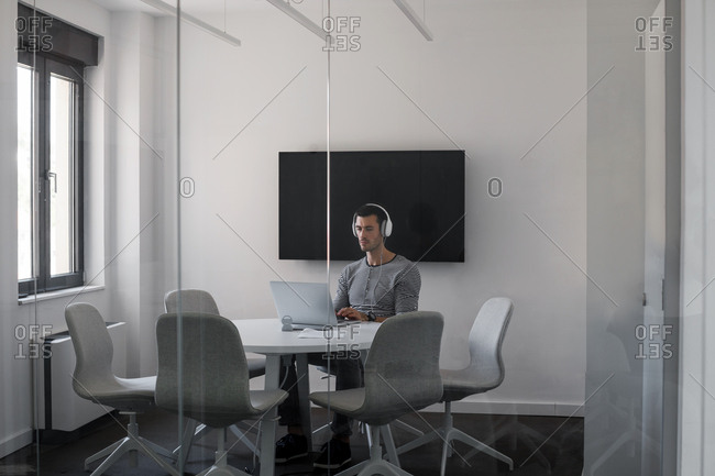 Young businessman using headphones and laptop at video conference room.