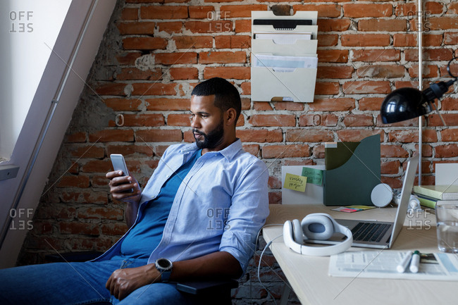 Casual businessman sitting at his office and typing on his cell phone.